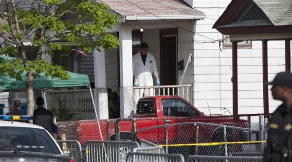 John Makely / NBC News An FBI investigator exits the house on Seymour Ave.