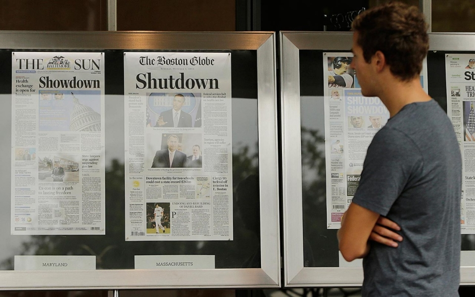 A man reads morning newspapers from around the U.S. at the Newseum in Washington, Oct. 1, 2013. Gary Cameron/Reuters