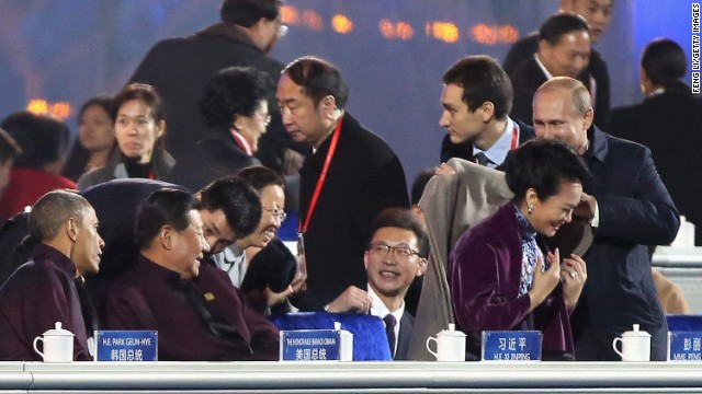 China's similar First Lady is seen accepting a shawl from Russian President Putin which she quickly slips off.