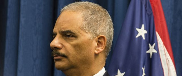 U.S. Attorney General Eric Holder listens as Steve Dettlebach, U.S. attorney general for the Northern District of Ohio, speaks to reporters at a press conference on Dec. 4, 2014 in Cleveland. (Photo by Angelo Merendino/Getty Images) | Angelo Merendino via Getty Images