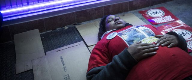 NEW YORK, NY - DECEMBER 11: Erica Garner, daughter of Eric Garner, lays down in the spot where her father died during a die-in, alongside other people protesting the Staten Island, New York grand jury's decision not to indict a police officer involved in the chokehold death of Eric Garner in July, on the night of December 11, 2014 in the Staten Island Neighborhood of New York City. Protests have continued throughout the country since the Grand Jury's decision was announced last week. (Photo b   Andrew Burton via Getty Images