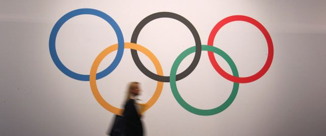 A woman walks in front of a board showing Olympics rings at the 127th International Olympic Committee session in Monaco, Monday, Dec. 8, 2014. (AP Photo/Lionel Cironneau) | ASSOCIATED PRESS