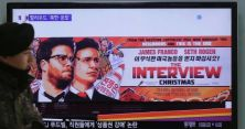 "A South Korean army soldier walks near a TV screen showing an advertisement of Sony Pictures Entertainment's ""The Interview"" at the Seoul Railway Station. (Ahn Young-Joon/AP)"