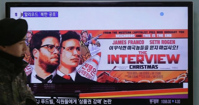 """A South Korean army soldier walks near a TV screen showing an advertisement of Sony Pictures Entertainment's """"The Interview"""" at the Seoul Railway Station. (Ahn Young-Joon/AP)"""