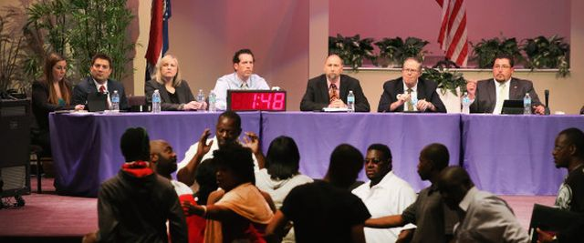 Ferguson Mayor James Knowles (seated far right) and city council members wait until angry residents calm down during a council meeting on Sept. 9, 2014. | Scott Olson via Getty Images