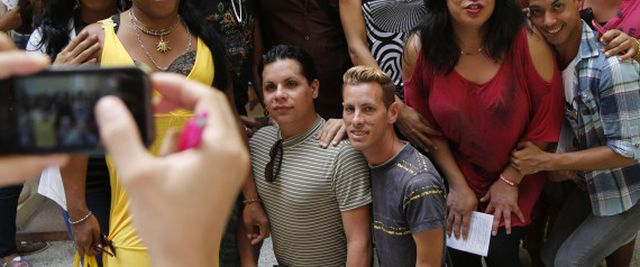 "Members of Cuba's LGBT community pose for pictures around U.S. photographer Byron Motley, center top, at his photo exhibit after a press conference that announced upcoming events to mark International Day Against Homophobia, at the Cuban National Center for Sex Education in Havana, Cuba, Tuesday, May 5, 2015. Motley inaugurated his exhibition titled ""Continuing Forward"" on Tuesday, which includes portraits of Cuba's LGBT community. International Day Against Homophobia is marked on May 17. (AP Ph 