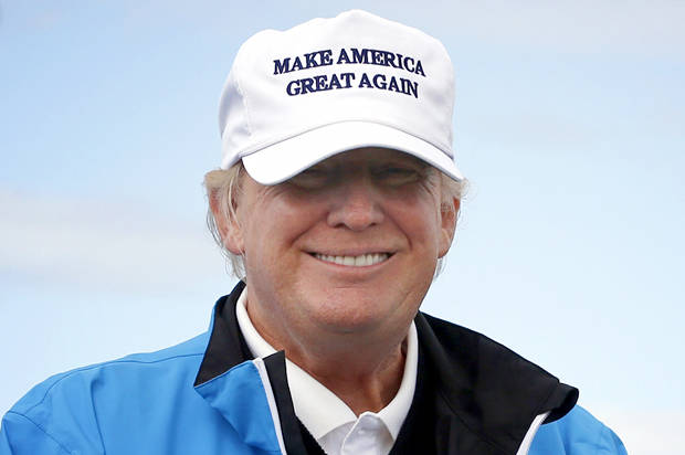 Presidential contender Donald Trump poses for the media during the third day of the Women's British Open golf championship on the Turnberry golf course in Turnberry, Scotland, Saturday, Aug. 01, 2015. (AP Photo/Scott Heppell)