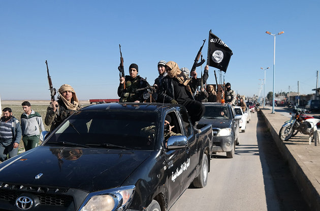 In this photo released on May 4, 2015, by a militant website, which has been verified and is consistent with other AP reporting, Islamic State militants pass by a convoy in Tel Abyad town, northeast Syria. In contrast to the failures of the Iraqi army, in Syria Kurdish fighters are on the march against the Islamic State group, capturing towns and villages in an oil-rich swath of the country's northeast in recent days, under the cover of U.S.-led airstrikes. (Militant website via AP)