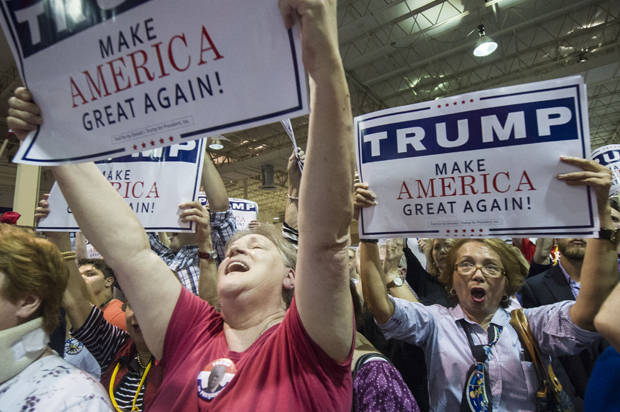 Supporters Kathleen Hastings, left, and Elizabeth Musngi, right, cheers Republican presidential candidate Donald Trump as he speaks during a campaign rally held at the North Atlanta Trade Center, Saturday, Oct., 10, 2015, in Norcross, Ga. (AP Photo/John Amis)