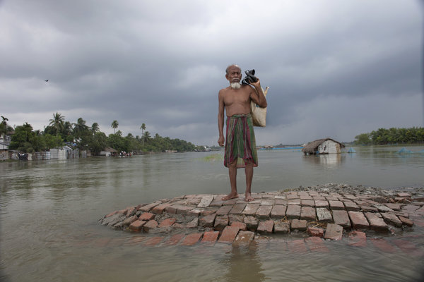 SATKHIRA, KHULNA, BANGLADESH - 2011/09/10: A flood-affected man stands on high land waits for a boat. 10 September 2011, Satkhira, Bangladesh Bangladesh is one of the countries most vulnerable to the effects of climate change. The regular and severe natural hazards that Bangladesh already suffers from tropical cyclones, river erosion, flood, landslides and drought are all set to increase in intensity and frequency as a result of climate change. Sea level rise will increasingly inundate coastal land in Bangladesh and dramatic coastal and river erosion will destroy lands and homes. These and the many other adverse effects of climate change will severely impact the economy and development of the country.One of the most dramatic impacts will be the forced movement of people throughout Bangladesh as a result of losing their homes, lands, property and livelihoods to the effects of climate change. While it is impossible to predict completely accurate figures of how many people will be displaced by climate change, the best current estimates state that sea level rise alone will displace 18 million Bangladeshis within the next 40 years. The vast majority of these people will be displaced within Bangladesh not across international borders presenting the Government with enormous challenges, particularly when it comes to finding places to live and work for those displaced. (Photo by Probal Rashid/LightRocket via Getty Images)