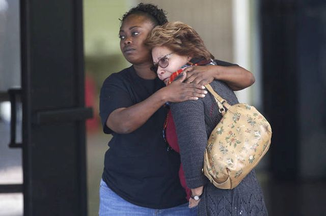 Two women embrace at a community center where family members are gathering to pick up survivors after a shooting rampage that killed multiple people and wounded others at a social services center in San Bernardino, Calif., Wednesday, Dec. 2, 2015. (AP Photo/Jae C. Hong)