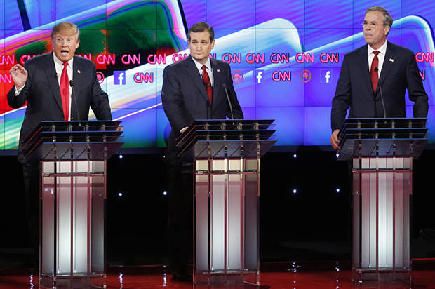 Donald Trump, left, speaks as Ted Cruz, center, and Jeb Bush look on during the CNN Republican presidential debate at the Venetian Hotel & Casino on Tuesday, Dec. 15, 2015, in Las Vegas. (AP Photo/John Locher)