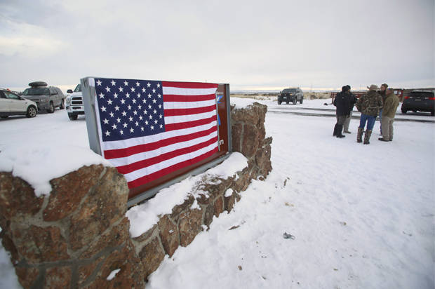 A U.S. flag covers a sign at the entrance of the Malheur National Wildlife Refuge near Burns, Oregon January 3, 2016. A group of self-styled militiamen occupied the headquarters of a U.S. wildlife refuge in eastern Oregon in a standoff with authorities, officials and local media reports said on Sunday, in the latest dispute over federal land use in the West. REUTERS/Jim Urquhart - RTX20WTM