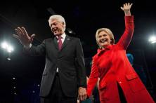 Former U.S. President Bill Clinton (L) and Democratic presidential candidate Hillary Clinton greet the crowd at the end of the Jefferson-Jackson Dinner in Des Moines, Iowa October 24, 2015. REUTERS/Mark Kauzlarich - RTX1T325