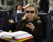 FILE - In this Oct. 18, 2011, file photo, then-Secretary of State Hillary Rodham Clinton checks her Blackberry from a desk inside a C-17 military plane upon her departure from Malta, in the Mediterranean Sea, bound for Tripoli, Libya. The Obama administration is confirming, Friday, Jan. 29, 2016, for the first time that Hillary Clinton's unsecured home server contained some closely guarded secrets, including material requiring one of the highest levels of classification. (Kevin Lamarque/Pool Photo via AP, File)