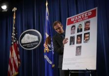 © Provided by AFP US Department of Justice employee puts up a poster of seven Iranians indicted on computer hacking charges by a grand jury in the Southern District of New York