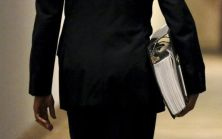 U.S. President Barack Obama carries a binder containing material on potential Supreme Court nominees as he walks towards the residence of the White House in Washington, February 19, 2016. REUTERS/Kevin Lamarque