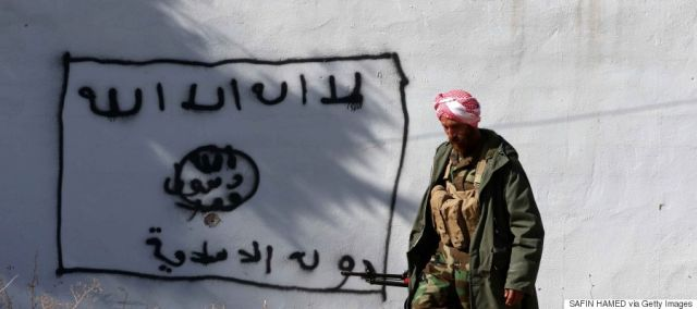 "A Kurdish fighter walks by a wall bearing a drawing of the flag of the Islamic State (IS) group in the northern Iraqi town of Sinjar, in the Nineveh Province, on November 13, 2015. Iraqi Kurdish leader Massud Barzani announced the ""liberation"" of Sinjar from the Islamic State group in an assault backed by US-led strikes that cut a key jihadist supply line with Syria. AFP PHOTO / SAFIN HAMED (Photo credit should read SAFIN HAMED/AFP/Getty Images)"