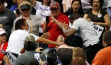 CORRECTS THAT THE SCUFFLE TOOK PLACE WHEN TRUMP WAS SPEAKING - A supporter of Republican presidential candidate Donald Trump, right, scuffles with an anti-Trump protester, as security, left, intervenes as Trump was speaking at a campaign rally Saturday, March 19, 2016, in Tucson, Ariz. (AP Photo/Ross D. Franklin)