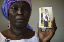 Martha Mark, the mother of kidnapped school girl Monica Mark cries as she displays her photo, Monday, May 19, 2014.