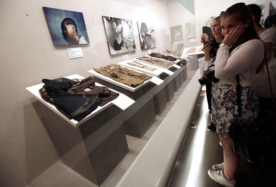 Tourists at the Hiroshima Peace Memorial Museum look at the bomb-singed remains of clothes that had been worn by Hiroshima's civilians during the attack. AP Photo