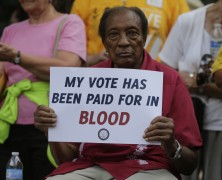 A man holds a protest sign at a rally in Winston-Salem, N.C., Monday, July 13, 2015 after the beginning of a federal voting rights trial challenging a 2013 state law.
