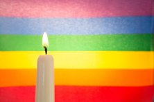 Candle against rainbow flag