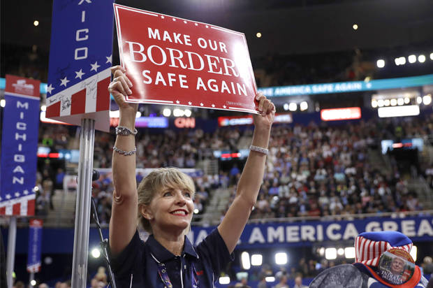 New Mexico delegate Susan Throckmorton holds up a sign during first day of the Republican National Convention in Cleveland, Monday, July 18, 2016. (AP Photo/Matt Rourke)