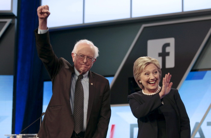 Democratic U.S. presidential candidates Senator Bernie Sanders and Hillary Clinton wave before the start of the Univision News and Washington Post Democratic U.S. presidential candidates debate in Kendall, Florida, March 9, 2016. REUTERS/Javier Galeano