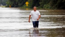 "Jeff Robinson wades through flood waters near his home in Baptist, La., Saturday, Aug. 13, 2016, as he seeks a boat ride from state wildlife agents to pick up his wife and children. A slow-moving storm that has dumped almost a foot of rain in Louisiana parishes south and west and Mississippi counties north of the Mississippi-Louisiana state line, are in for more rain. National Guard soldiers and other officials in boats and helicopters plucked more than 1,000 people from their homes and cars as ""unprecedented, historic"" flooding swamped Louisiana, the governor said Saturday. (AP Photo/Rogelio V. Solis)"