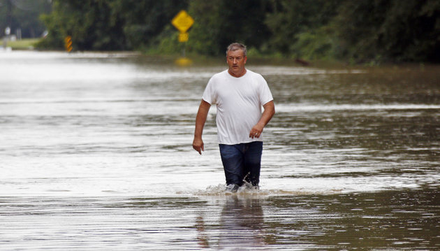 """Jeff Robinson wades through flood waters near his home in Baptist, La., Saturday, Aug. 13, 2016, as he seeks a boat ride from state wildlife agents to pick up his wife and children. A slow-moving storm that has dumped almost a foot of rain in Louisiana parishes south and west and Mississippi counties north of the Mississippi-Louisiana state line, are in for more rain. National Guard soldiers and other officials in boats and helicopters plucked more than 1,000 people from their homes and cars as """"unprecedented, historic"""" flooding swamped Louisiana, the governor said Saturday. (AP Photo/Rogelio V. Solis)"""