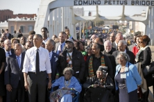 "U.S. President Barack Obama participates in a march across the Edmund Pettus Bridge in Selma, Alabama, March 7, 2015. The event comes on the 50th anniversary of the ""Bloody Sunday"" march at the bridge, where police and state troopers beat and used tear gas against peaceful marchers who were advocating against racial discrimination at the voting booth. REUTERS/Jonathan Ernst (UNITED STATES - Tags: POLITICS ANNIVERSARY SOCIETY) - RTR4SGNP"
