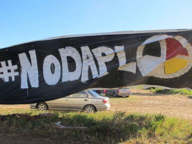 A banner protesting the Dakota Access oil pipeline is displayed at an encampment near North Dakota's Standing Rock Sioux Reservation. CREDIT: AP Photo/James MacPherson