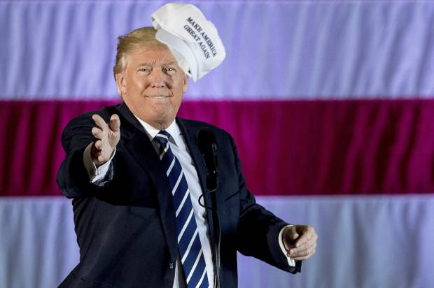 President-elect Donald Trump throws a hat into the audience while speaking at a rally in a DOW Chemical Hanger at Baton Rouge Metropolitan Airport, Friday, Dec. 9, 2016, in Baton Rouge, La. (AP Photo/Andrew Harnik)(Credit: AP)