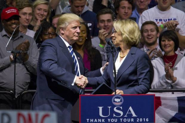 "President-elect Donald J. Trump greets Betsy DeVos, his choice for education secretary, during his ""USA Thank You Tour"" at the DeltaPlex in Walker, Mich., Friday, Dec. 9, 2016. (Cory Morse/The Grand Rapids Press-MLive.com via AP)(Credit: AP)"
